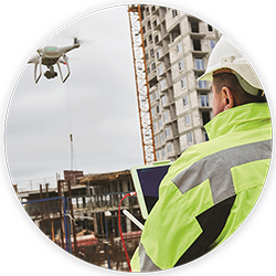 man in white hard hat supervising a drone survey